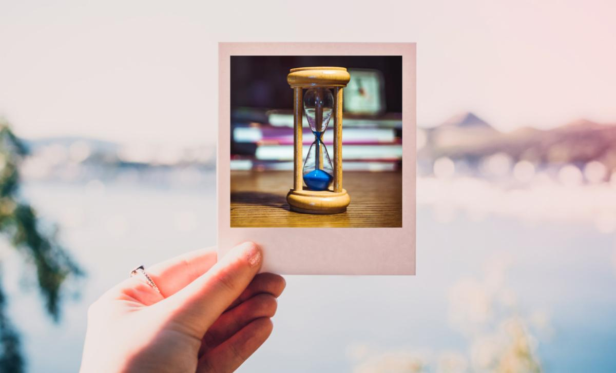 a hand holding a Polaroid image of an hourglass
