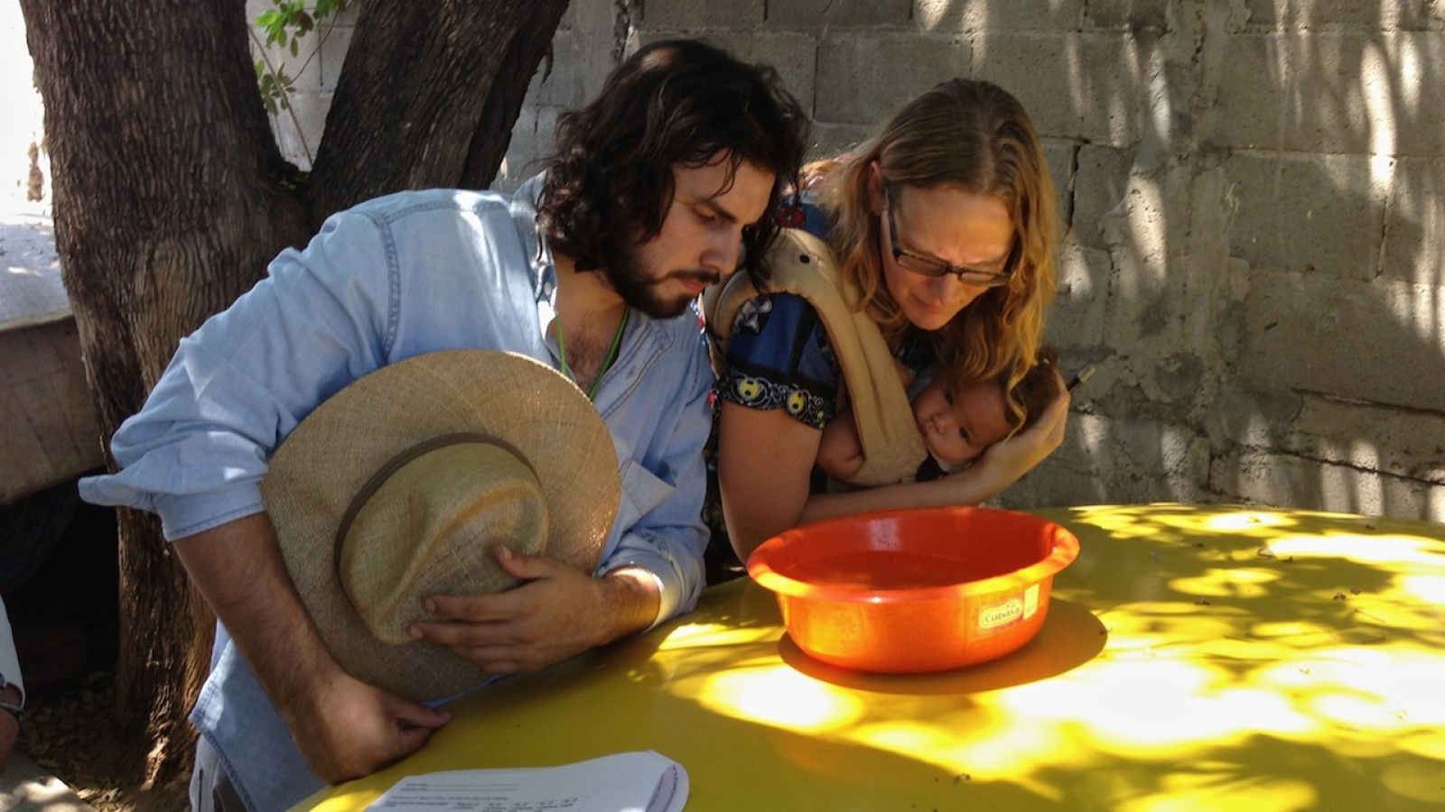 An image of a man and woman (holding a child) looking into a bowl of water